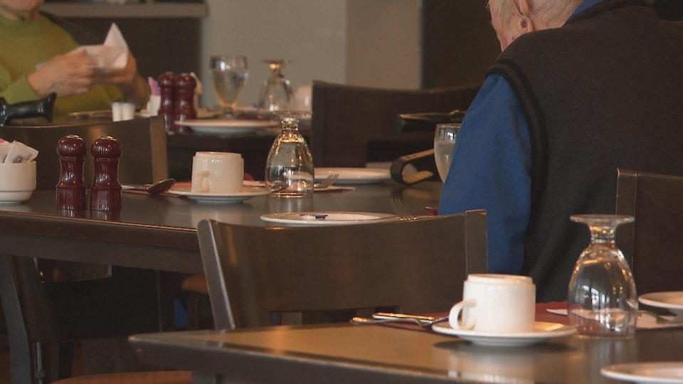 Des aînés assis à des tables dans la salle à manger commune.