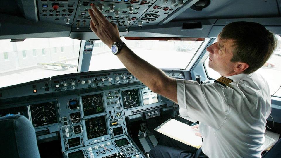 Un pilote d'Air Canada, dans la cabine de pilotage d'un Airbus A340-600, se prépare pour le départ d'un vol à l'aéroport Montréal-Trudeau.
