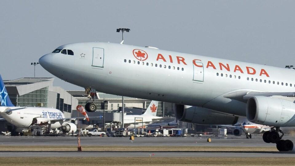 Un avion d'Air Canada passe devant un autre d'Air Transat à l'aéroport Montréal-Trudeau.