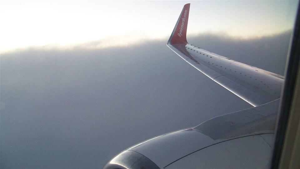 Plan serré de l'aile d'un avion vu par un hublot.