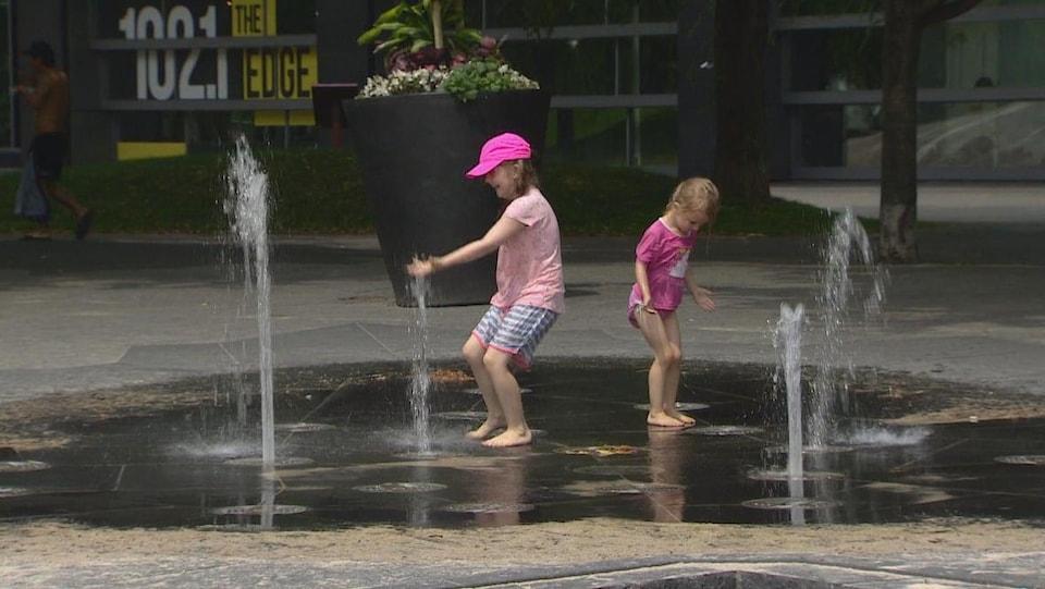 Deux petites filles jouent dans une aire de jeux d'eau.