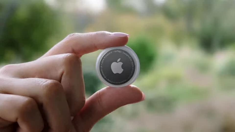 Une main qui tient un objet rond à l'effigie du logo d'Apple.