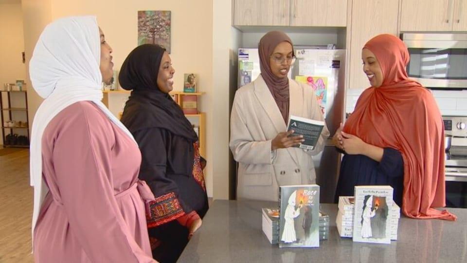 Les quatre soeurs regardent la couverture d'un livre.