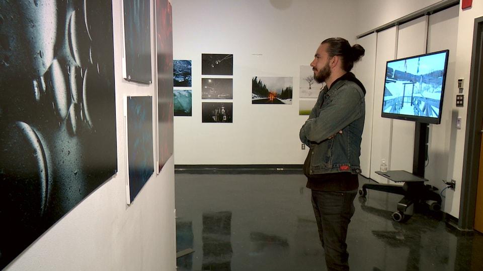 Alexandre Durastel devant des photos de l'exposition des finissants.