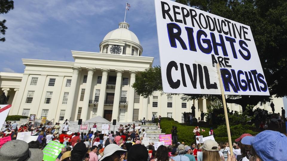 Des dizaines de personnes brandissent des pancartes devant le Capitole.