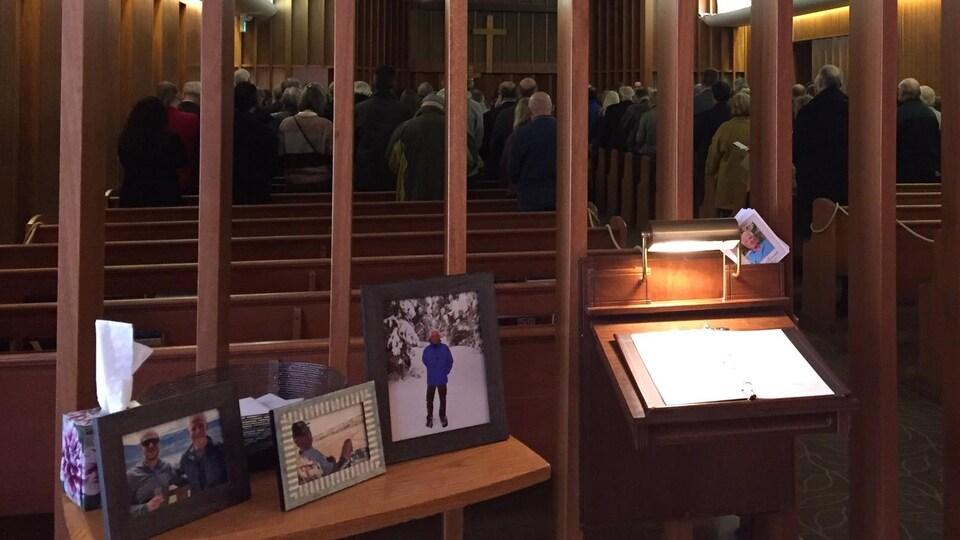 Dans un centre funéraire, une table avec des photos d'Alain Clermont, et une écritoire avec un carnet de condoléances. En arrière-plan, des gens prient debout.