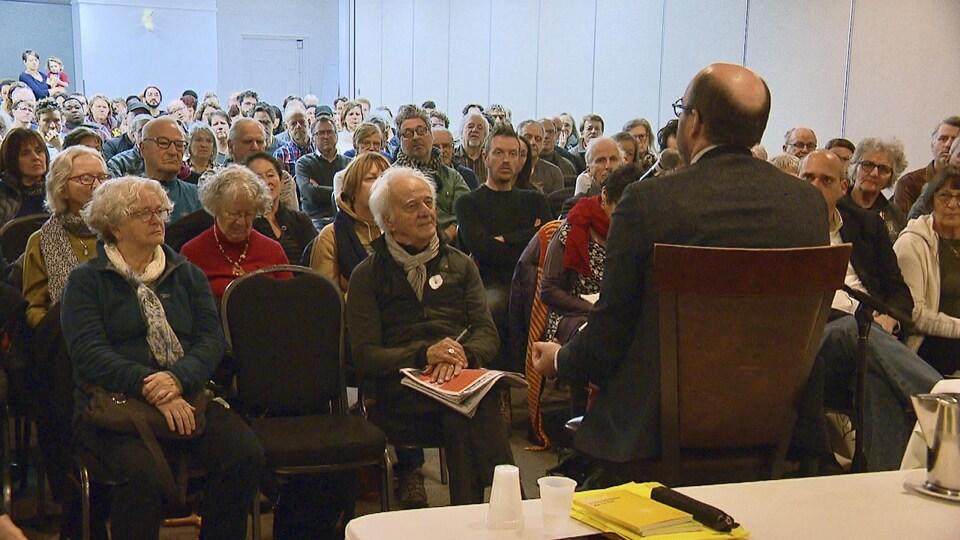Une salle bondée de citoyens attentifs devant Alain Deneault.