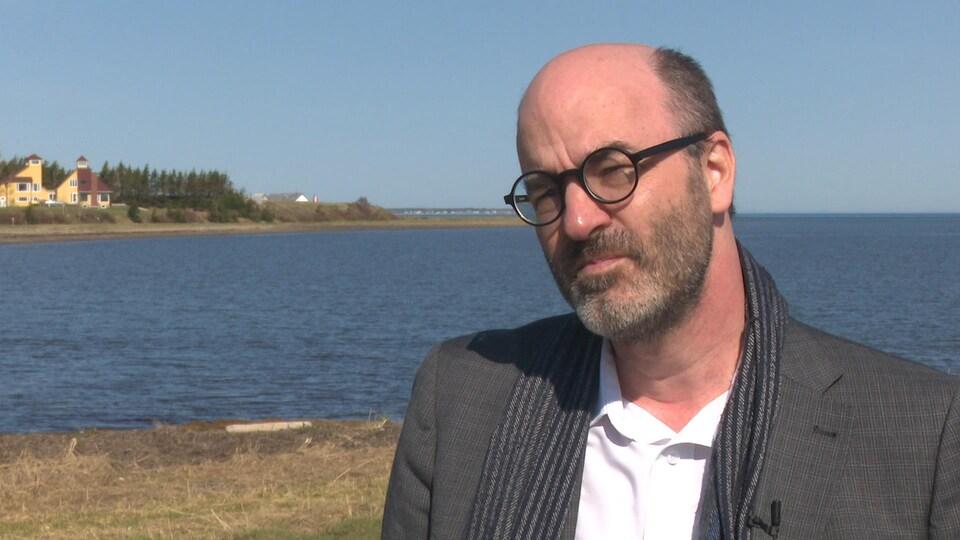 Un homme accorde une entrevue à la caméra, au bord de l'eau.