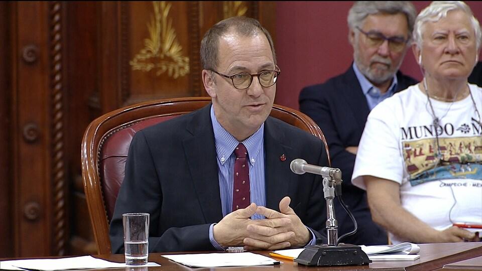 Alain Fortier, les mains jointes, s'adressant aux membres de la commission  parlementaire des institutions.