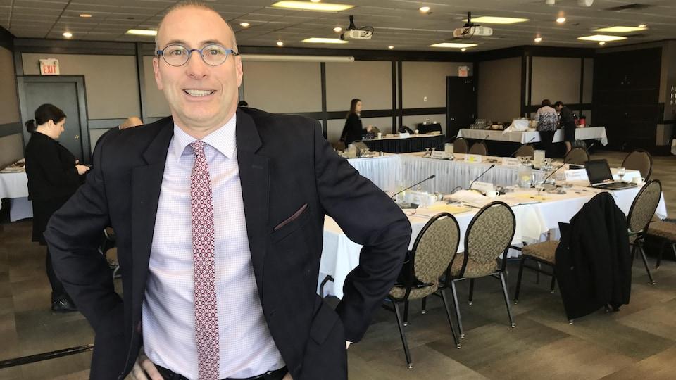 Alain Laberge se tient debout en costume-cravate dans une salle de conférence. Il est souriant avec les mains sur les hanches.