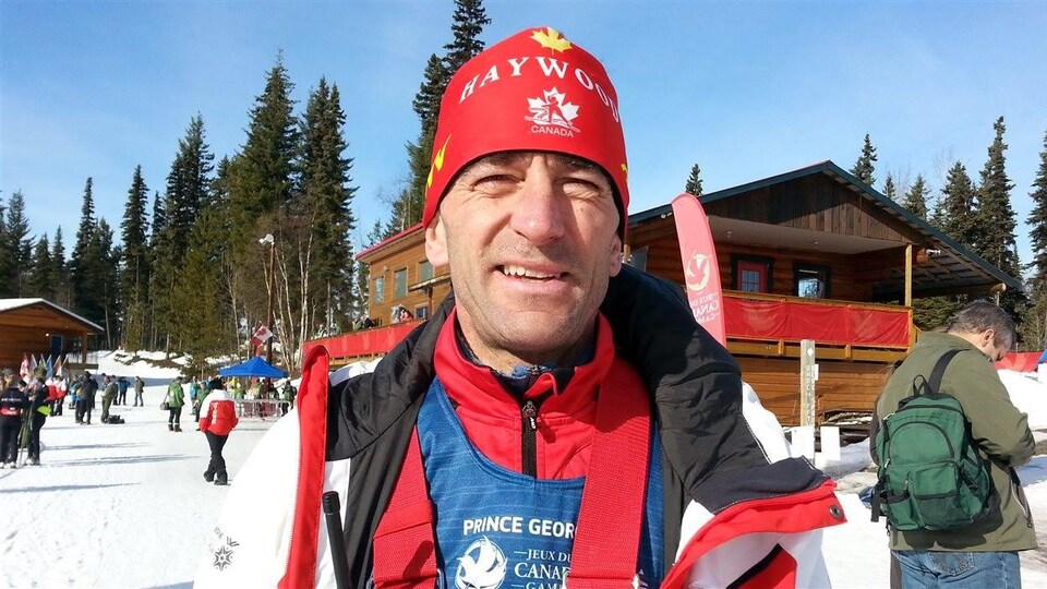 Alain Masson en tenue de ski, avec une station de ski en arrière plan.