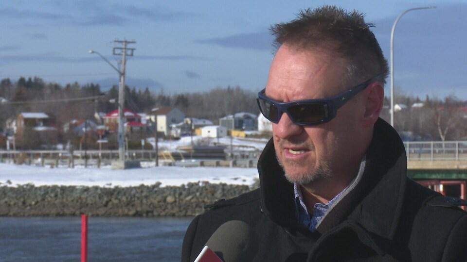 Le policier retraité Alain Tremblay en entrevue avec Radio-Canada, dans un paysage extérieur d'hiver.
