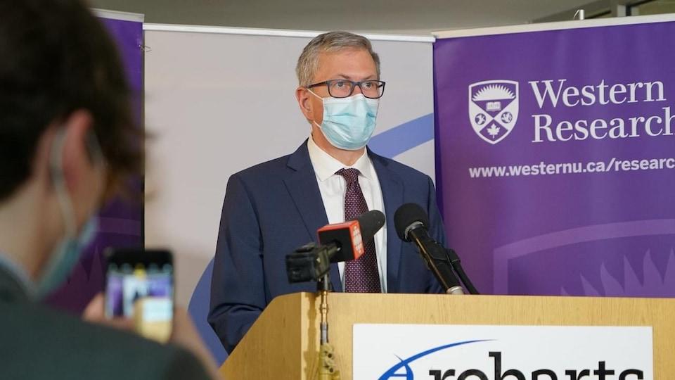 Un homme à un podium porte un masque.
