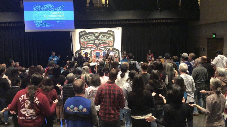 Un groupe de personnes au centre d'une salle avec de grandes affiches aux symboles autochtones.