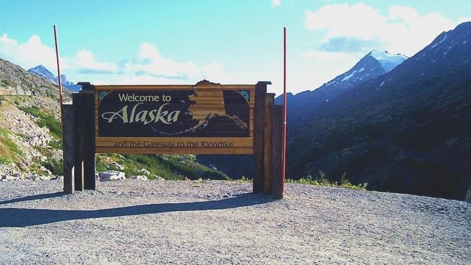 Panneau de bienvenue en Alaska devant des montagnes en été.