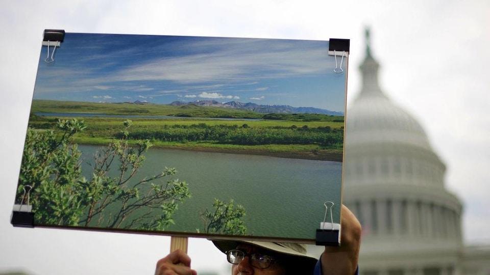 Quelqu'un tient la photo d'un paysage devant la Maison-Blanche à Washington.