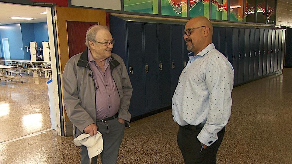 Les deux hommes discutent dans un corridor, devant une rangée de casiers.
