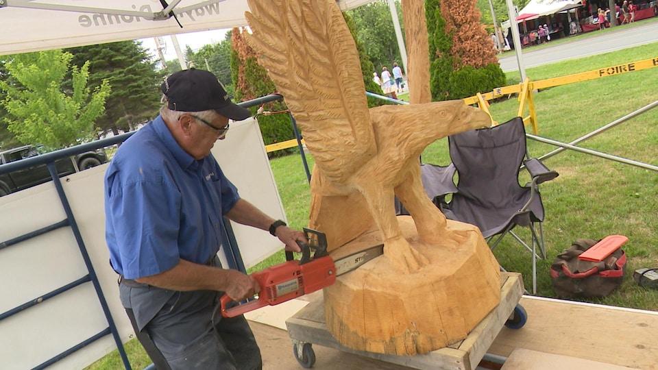 Un homme âgé avec une scie mécanique taille un aigle dans du bois.