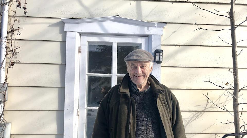L'artiste devant sa porte, à l'extérieur.