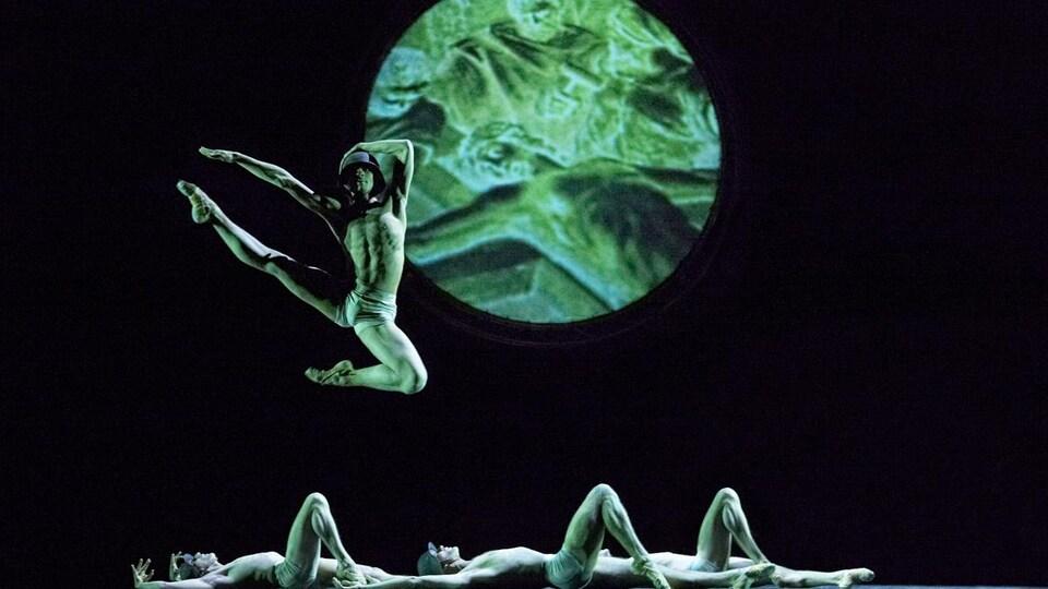 Trois hommes sont étendus sur le sol et un homme saute en l'air, devant une lune verte.