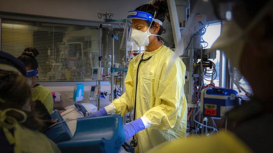 Une médecin masquée et en blouse jaune devant une civière sur laquelle est étendue un patient.