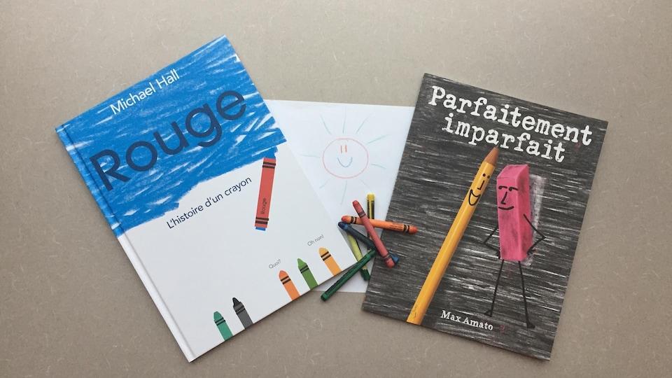 Les deux livres sont posés sur une table, de chaque côté d'une feuille blanche sur laquelle est dessiné un soleil rouge aux rayons verts. Cinq crayons de cire sont empilés entre les deux livres.