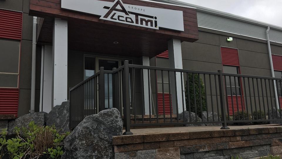 Le logo de l'entreprise est accroché à un bâtiment en béton.