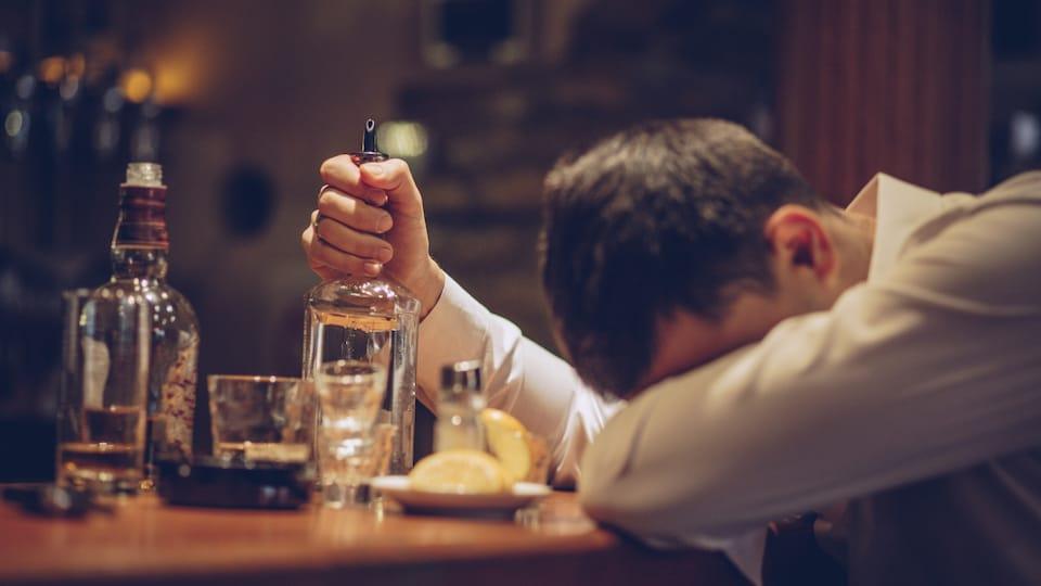 Un homme accoté à un bar avec des bouteilles d'alcool.