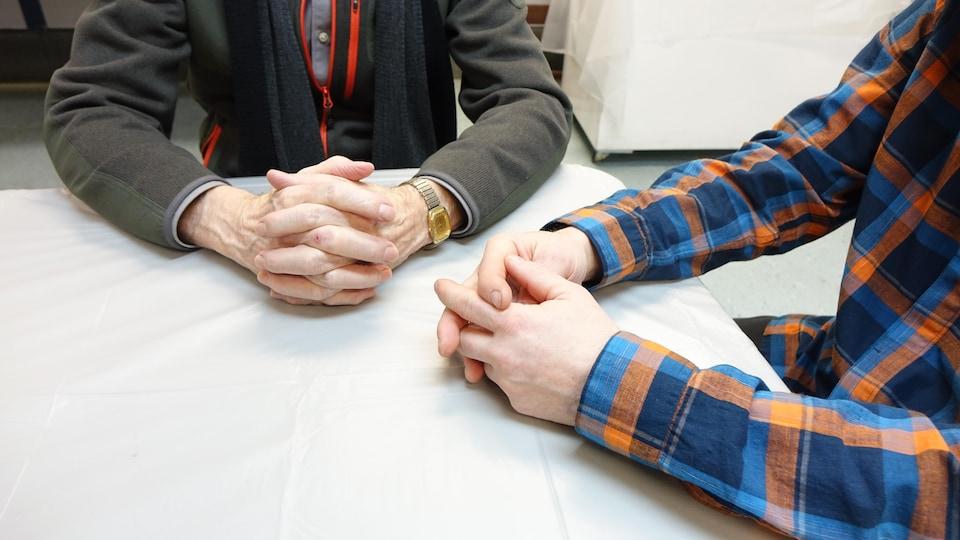 Les mains de deux hommes posées sur une table.