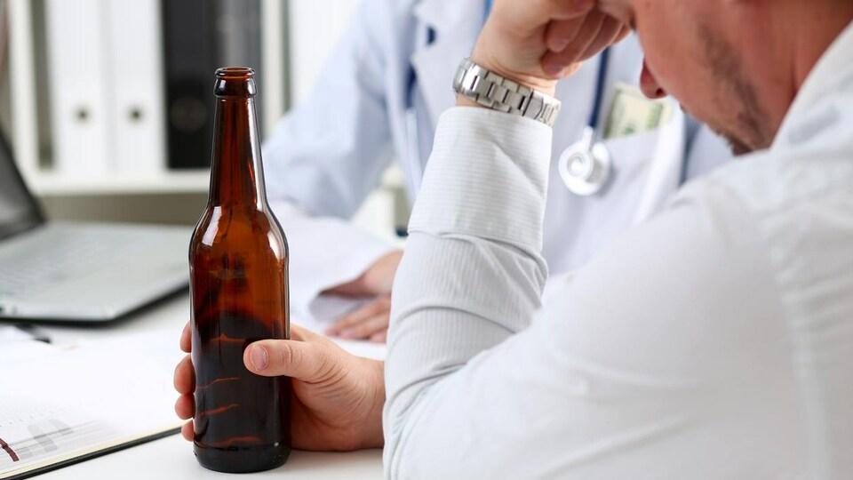 Un homme qui tient une bouteille de bière se trouve devant un médecin.