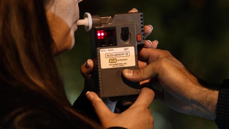 Une automobiliste passant l'alcootest lors d'un barrage routier à Surrey, en Colombie-Britannique, juste avant minuit, le 24 septembre 2010. La conductrice, dont le taux d'alcool dans le sang était de .05, a immédiatement reçu une amende de 200 $ et une interdiction de conduire pendant trois jours.