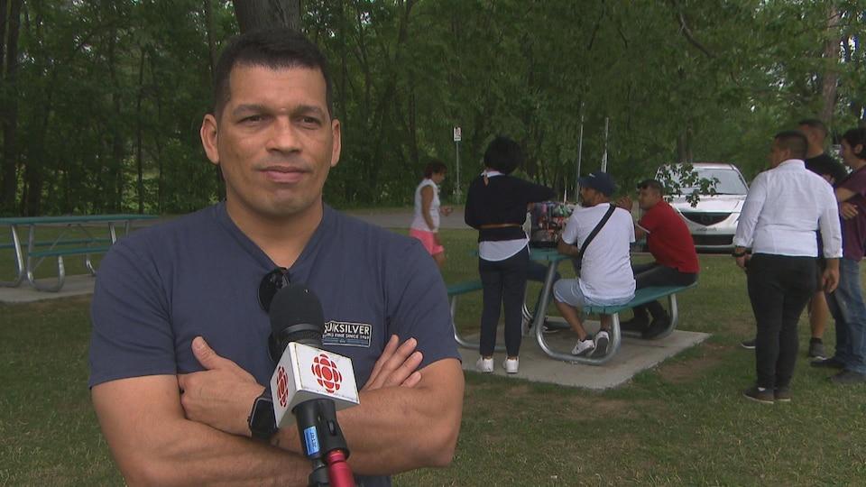 Un homme les bras croisés dans un parc fait une entrevue.