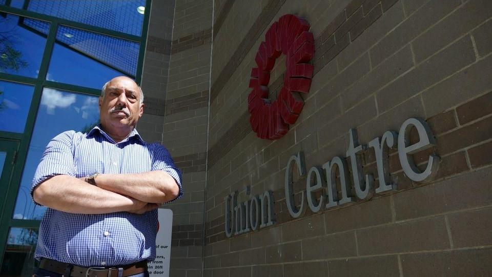 Un homme moustachu croise les bras devant l'immeuble de Winnipeg qui abrite les bureaux de plusieurs syndicats.