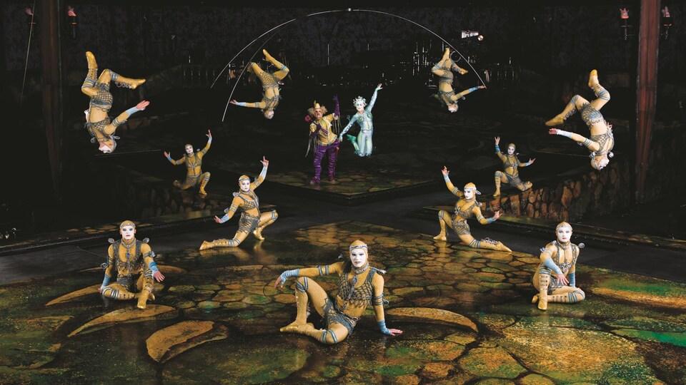 Des artistes du Cirque du Soleil prennent la pose sur scène, en costumes et en action, dans le décor du spectacle.