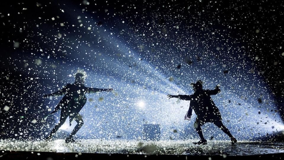 Deux silhouettes se découpent en ombres chinoises sous des milliers de confettis tombant du ciel.