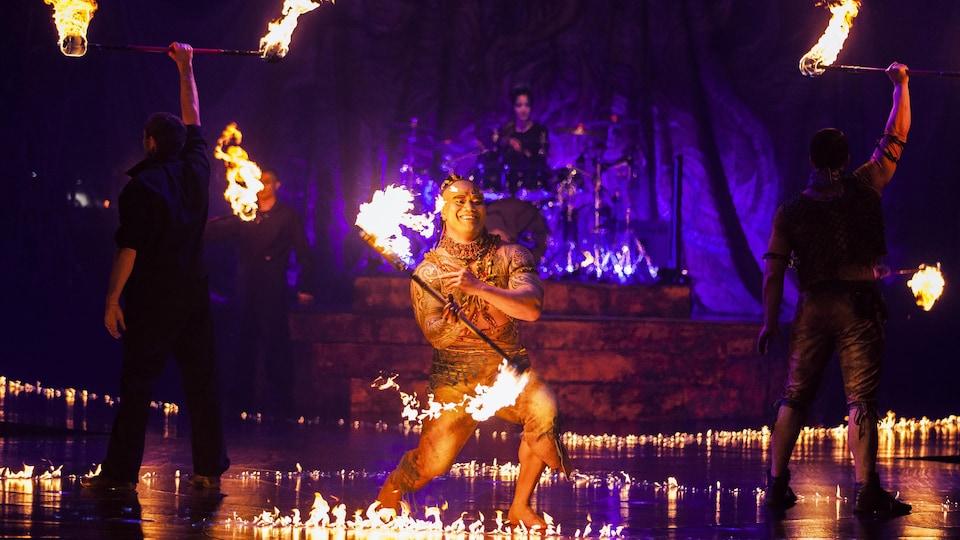 Un homme jongle avec une torche enflammée aux deux extrémités, alors que deux autres, de dos, tiennent aussi une torche à bout de bras. En arrière-plan, une femme joue de la batterie.