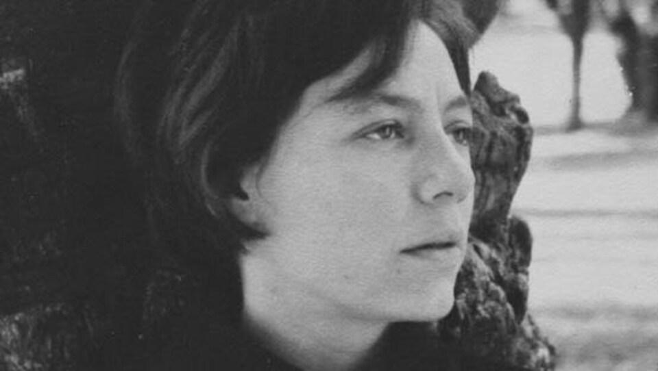 Portrait en noir et blanc de la poète Alejandra Pizarnik de trois-quarts, devant un tronc d'arbre.
