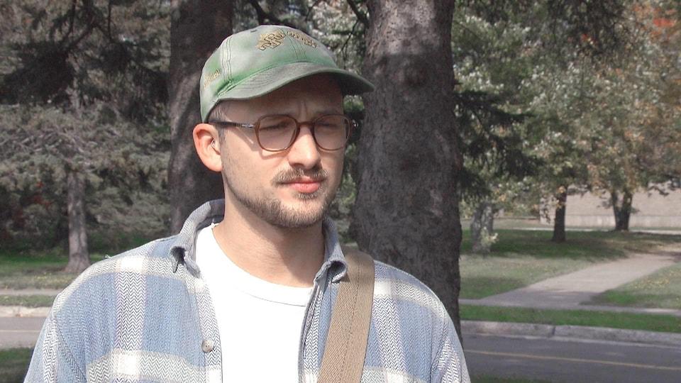 Alex Arseneau en entrevue à l'extérieur près d'un boisé.
