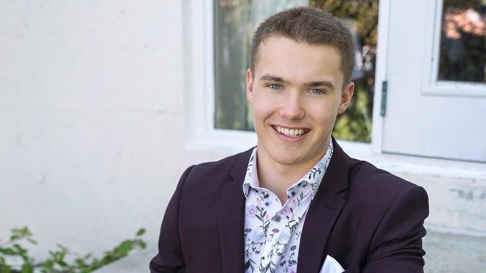 Le président de l'Association générale des étudiantes et étudiants du Cégep de Baie-Comeau, Alex Marin, assis à l'extérieur de son domicile.
