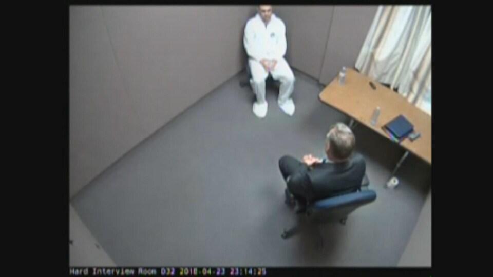 Capture d'écran montrant deux hommes assis l'un en face de l'autre dans une salle.