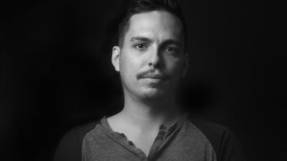 Portrait en noir et blanc, sur fond noir, d'Alex Noël. Le jeune homme porte une moustache.