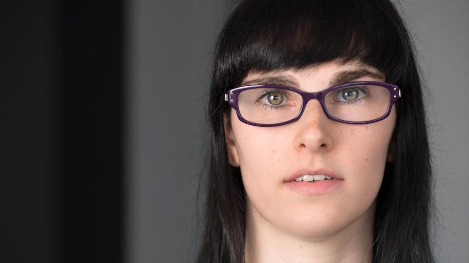 Portrait en couleur de l'autrice Alex Thibodeau sur fond gris : elle porte des lunettes mauves, un chandail gris, des cheveux bruns lâchés et une frange.