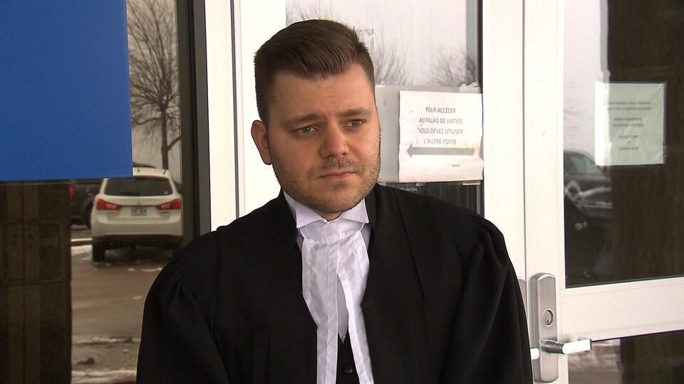 Alex Turcotte, en toge, donne une entrevue devant les portes du palais de justice.