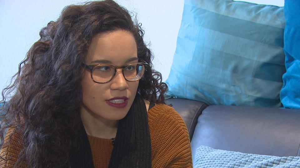 Une femme métisse aux longs cheveux noirs porte des lunettes et un chandail marron.