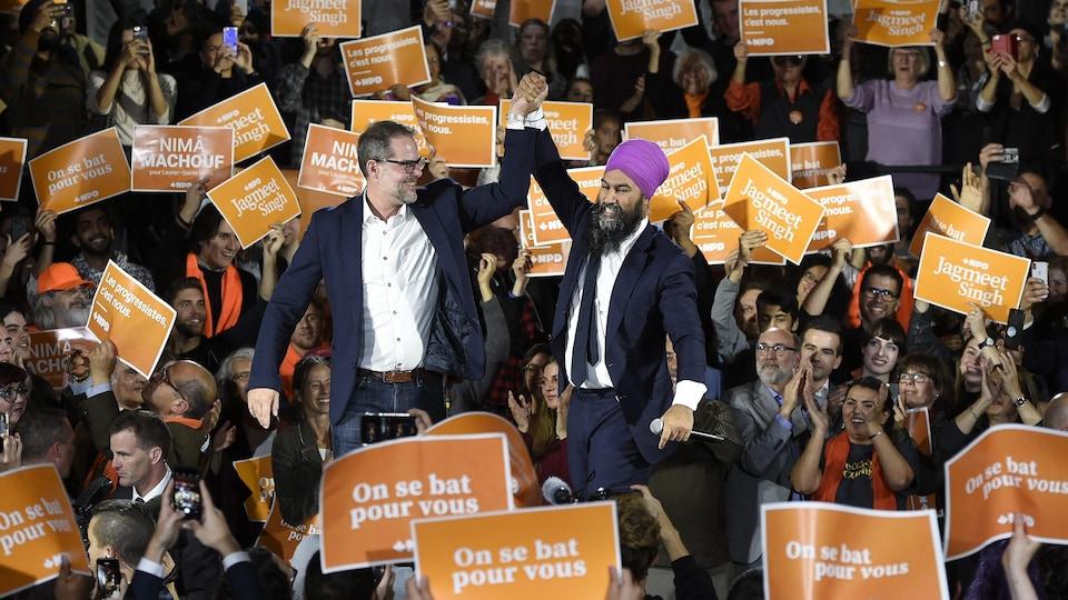 Alexandre Boulerice, à gauche, lève le bras aux côtés du chef du NPD, Jagmeet Singh, durant un rassemblement partisan.