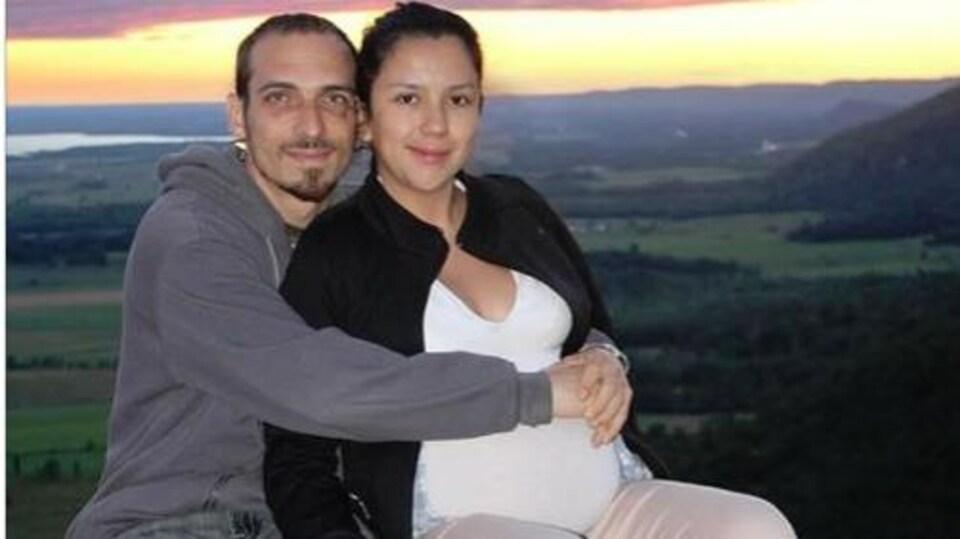 Alexandre et Jennifer qui est enceinte, enlacés, devant un coucher de soleil.