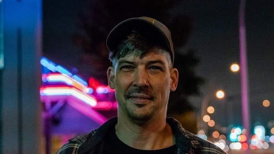 Un homme portant une casquette sourit.