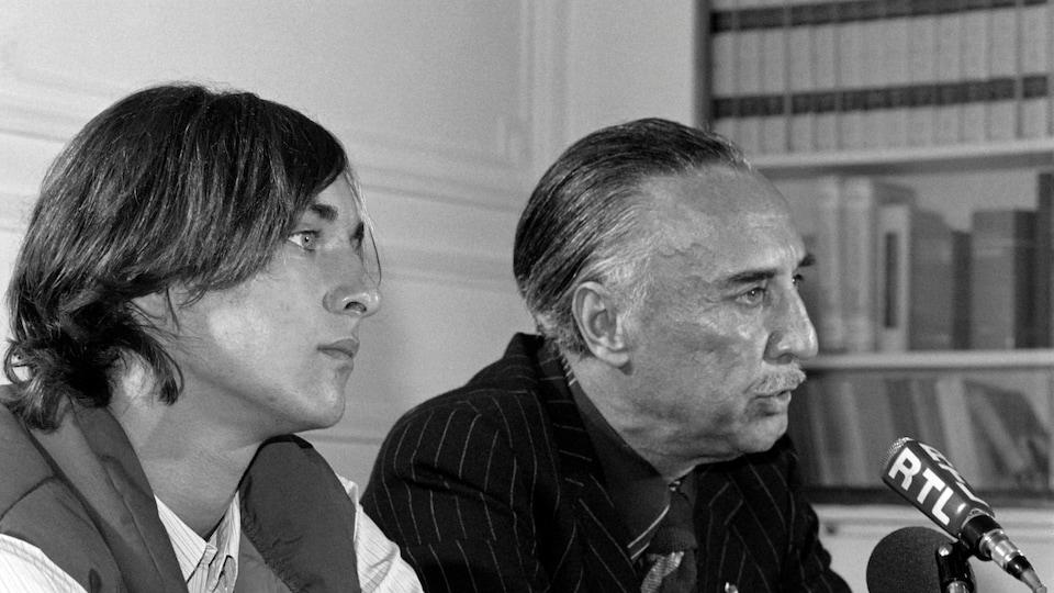 Le jeune homme et son père sont assis devant des micros.