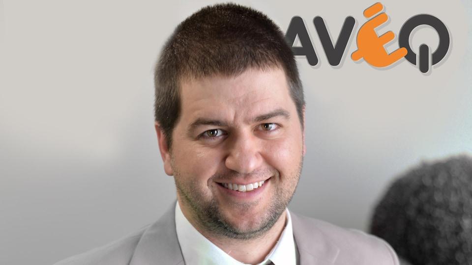 Le directeur général de l'Association des Véhicules Électriques du Québec (AVEQ) prend la pose avec le logo de l'organisme en arrière-plan.