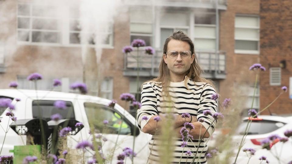 Alexandre Thibodeau pose entouré de fleurs.